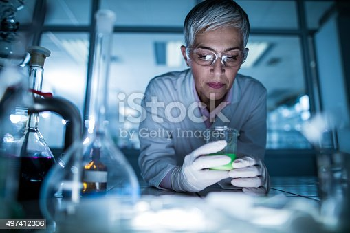 Mature chemist examining chemicals for her scientific research in laboratory.