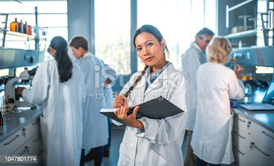 istock Female scientist writing in diary with team in lab 1047801774
