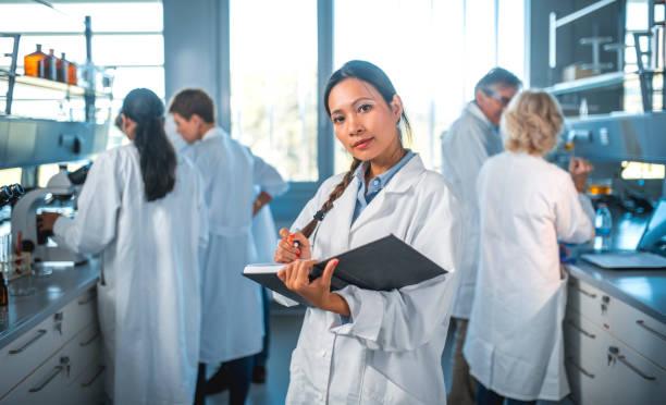 Wissenschaftlerin mit Team im Labor in Tagebuch zu schreiben – Foto