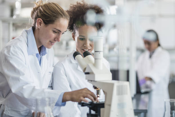 Female Scientists Beside a Microscope stock photo