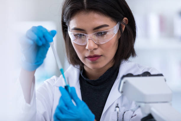Female scientists concentrates while preparing sample Focused mid adult female scientist uses a pipette and test tube while working in a laboratory. microbiologist stock pictures, royalty-free photos & images