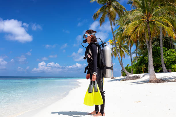 Female scuba diver stands on a tropical beach stock photo