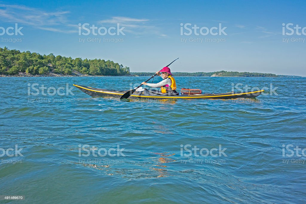 Female sea kayaker in the Stockholm archipelago, looking at island stock photo