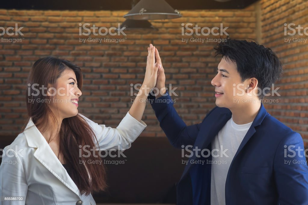 Female Secretary and Asian Business Joining hands with mutual success. stock photo