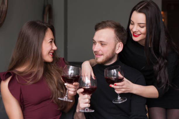 Female seduction at company party. Love triangle stock photo