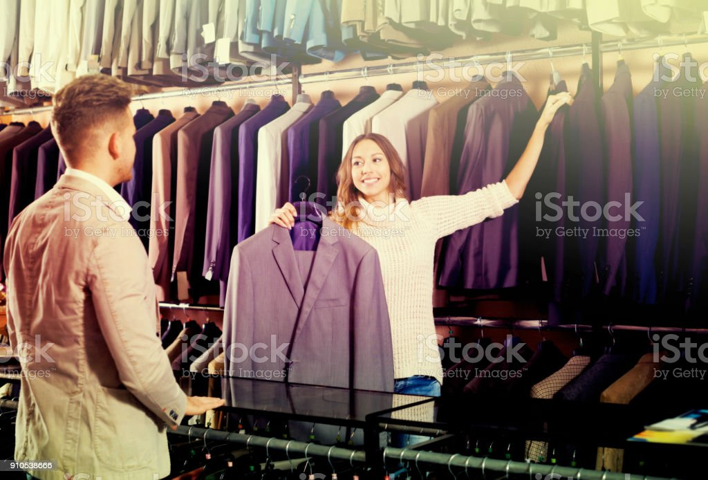 Female seller demonstrating numerous suits stock photo