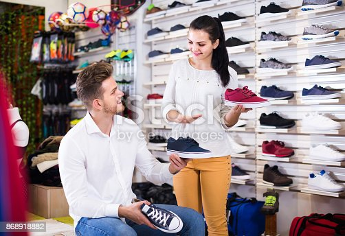 istock female seller demonstrating sneakers to customer in sports store 868918882