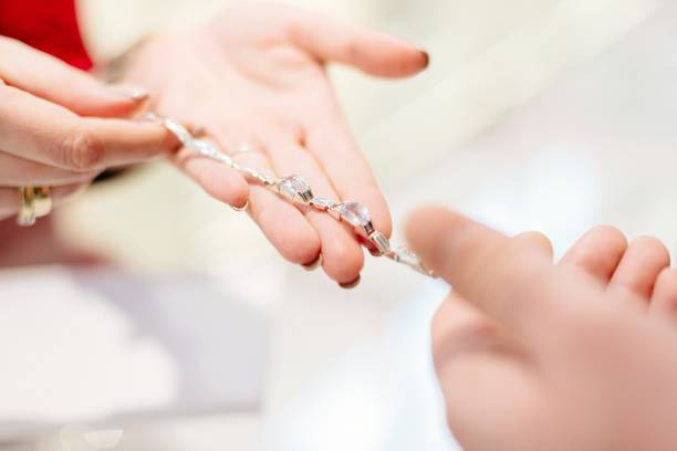 Female seller in a luxury jewelry store presents a bracelet Female seller in a luxury jewelry store presents a bracelet. Buying a present. Jewelry store. Woman jeweler jeweller stock pictures, royalty-free photos & images