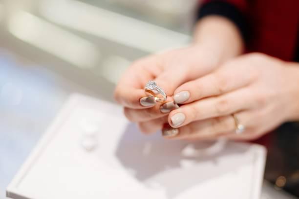 weibliche verkäufer in einem luxus-schmuck-shop präsentiert einen ring. - diamanten kaufen stock-fotos und bilder
