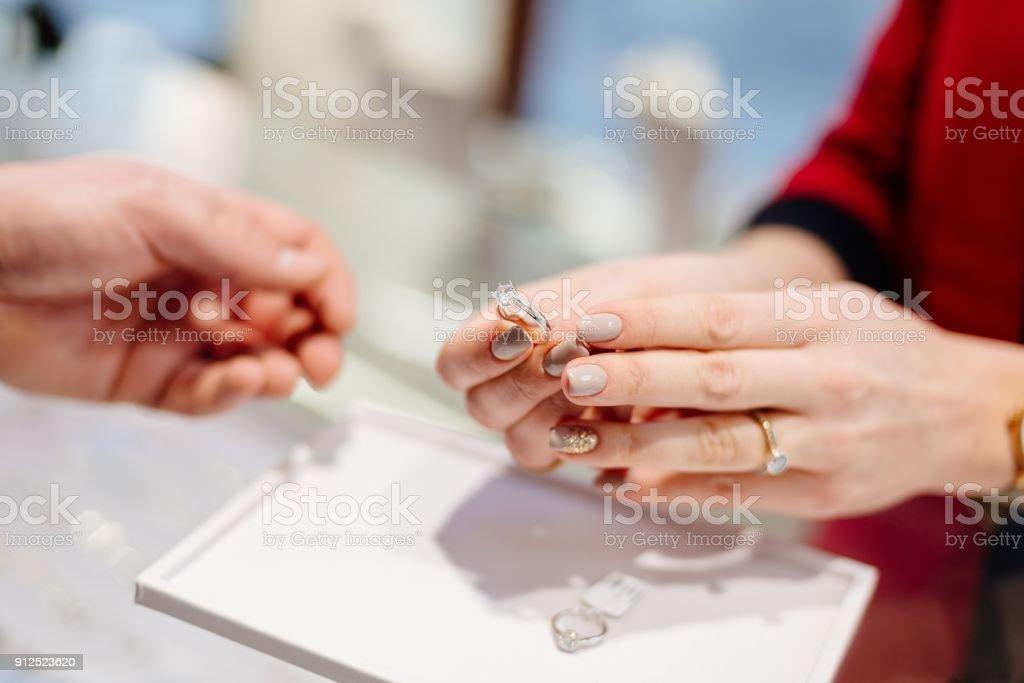 Kvinnliga säljaren i en lyx Smyckesbutik presenterar en ring. - Royaltyfri Affär Bildbanksbilder