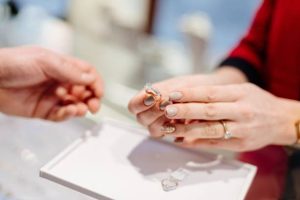 female seller in a luxury jewelry store presents a ring. - anello gioiello foto e immagini stock