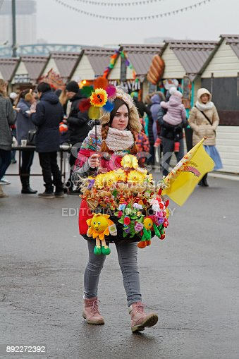 Moscow, Russia - March 12, 2016: Female seller of Russian Shrovetide small dolls in traditional colorful dresses and with a turntable at Russian national festival