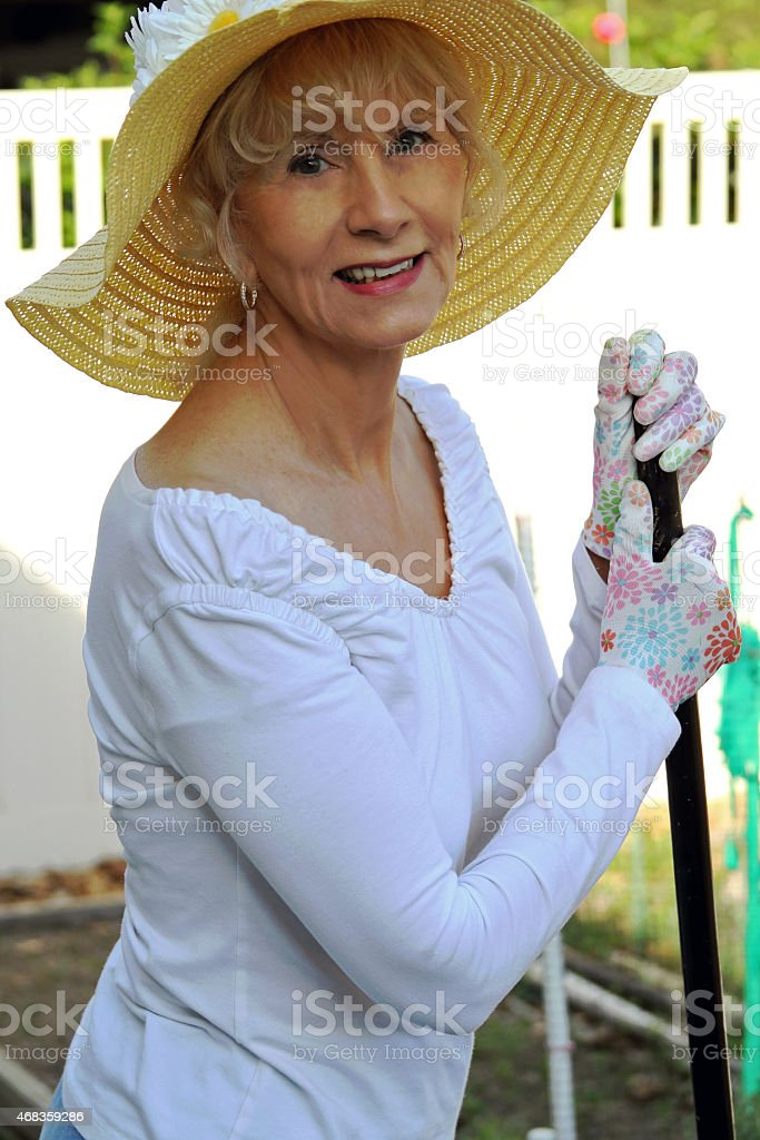 Female Senior Adult Resting On A Broom royalty-free stock photo