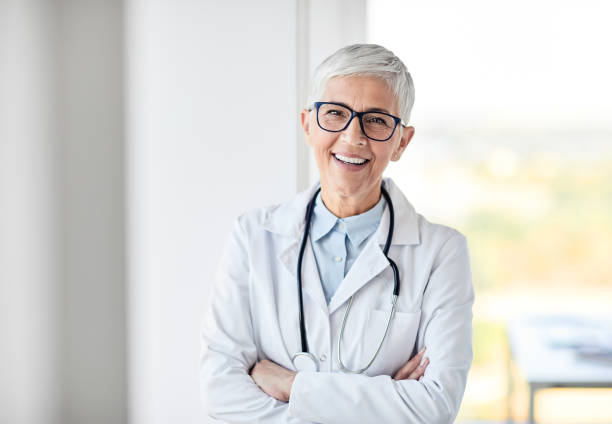 female senior doctor hospital medical clinic medicine health care portrait of a senior female doctor in a white coat with a stethoscope female doctor stock pictures, royalty-free photos & images