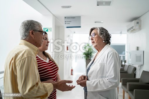 840514774istockphoto Female senior doctor talking about bad news and consoling sad family at hospital 1200988953