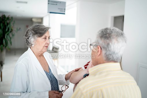 840514774istockphoto Female senior doctor talking about bad news and consoling sad family at hospital 1200990069