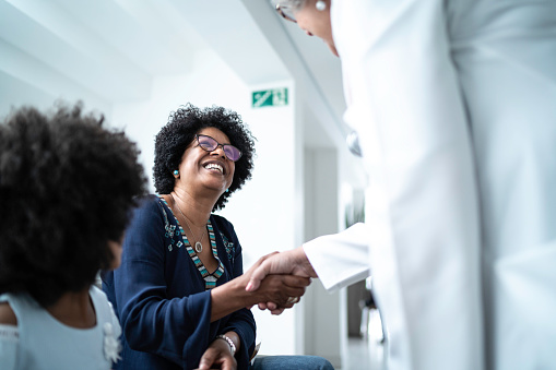 Female senior doctor welcoming / greeting mother and daughter at hospital