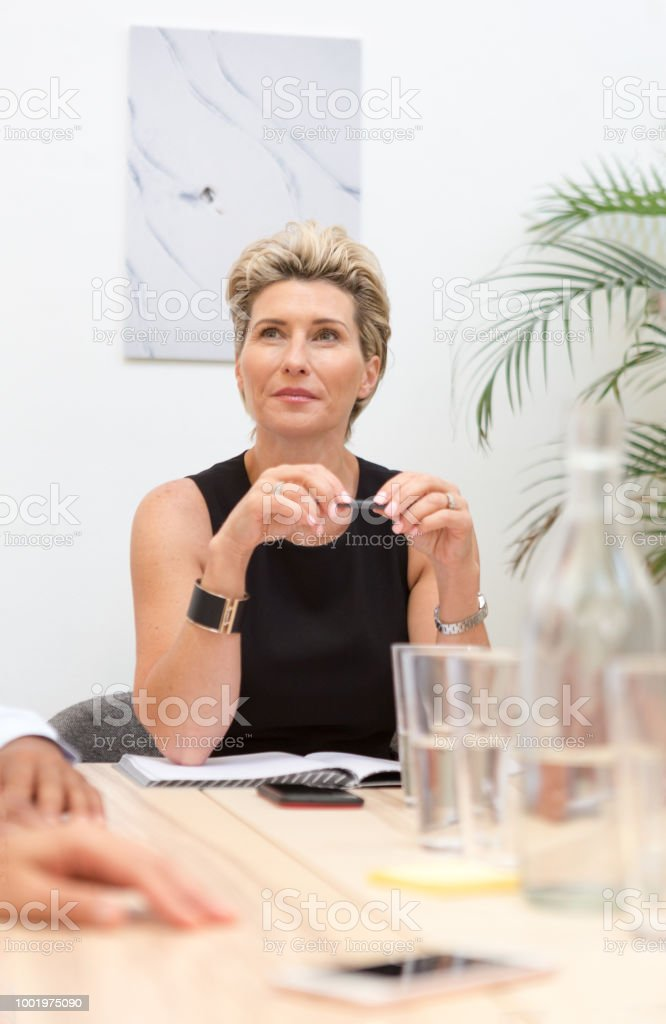 Female senior executive or manager in boardroom office meeting stock photo