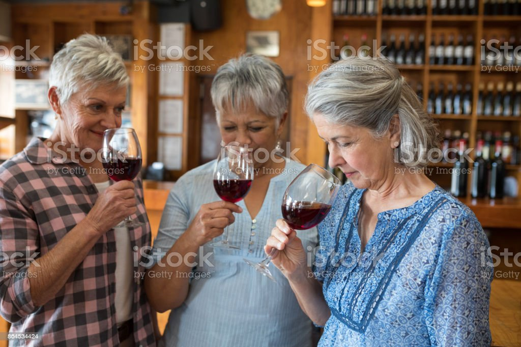 Smiling female senior friends having red wine in restaurant