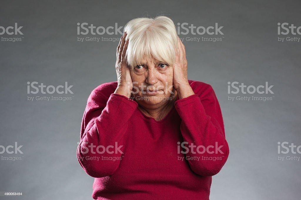 Female senior holding hands over ears stock photo
