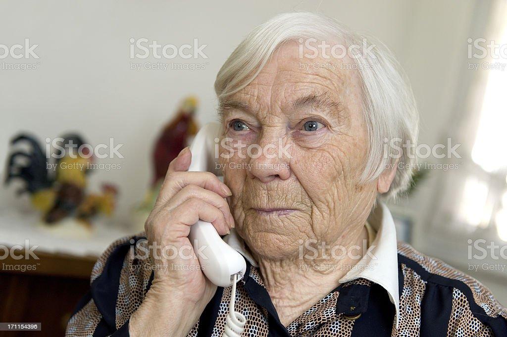 Female Senior is holding a phone and looks sad stock photo
