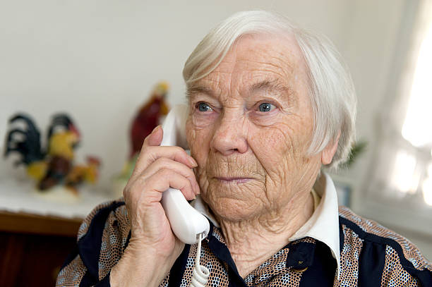 Female Senior is holding a phone and looks sad stock photo