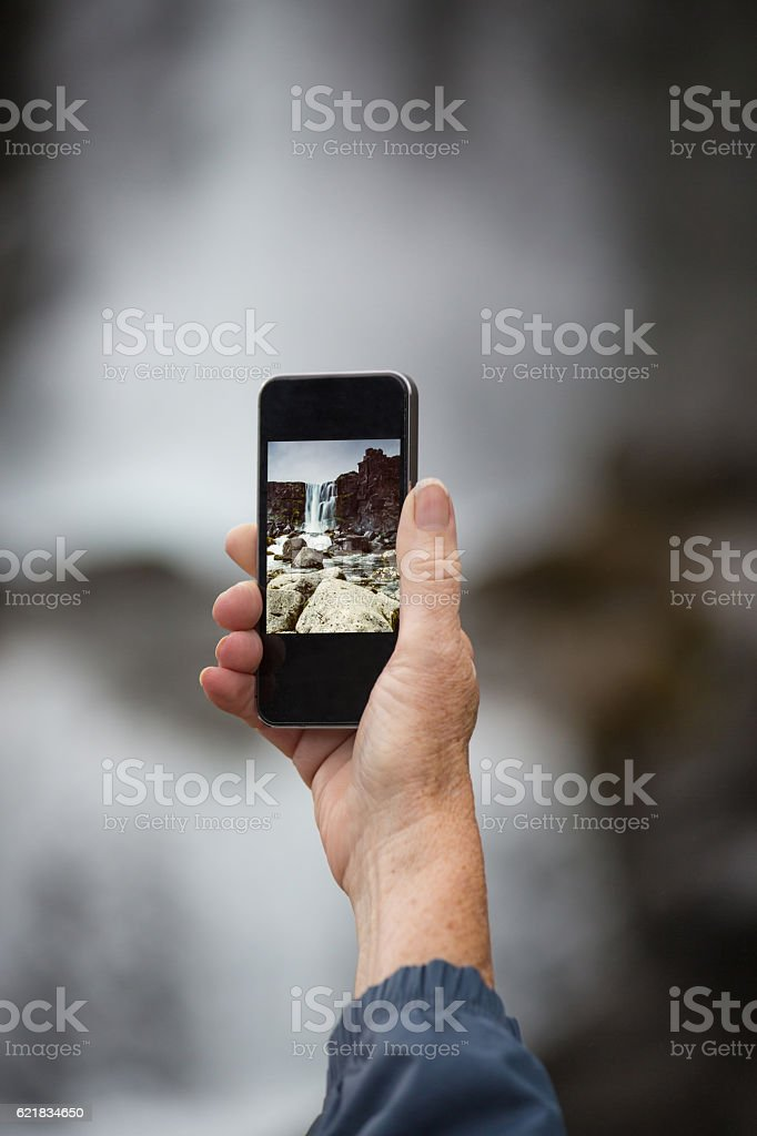 Female senior traveler photographing with smartphone the waterfa stock photo