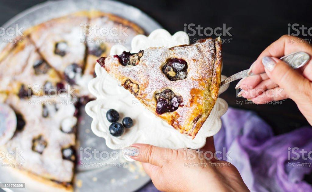 Female serving fruit sweet pie slice Female serving blueberry fruit sweet pie first person Adult Stock Photo
