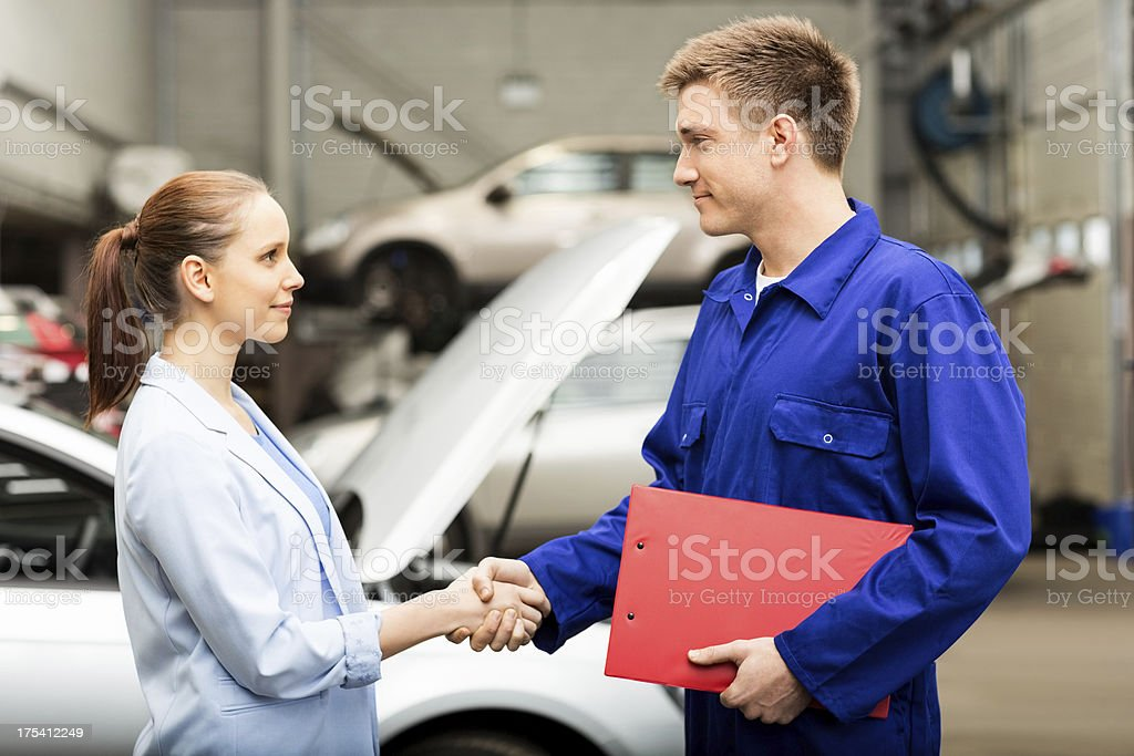 Female Shaking Hands With Car Mechanic royalty-free stock photo