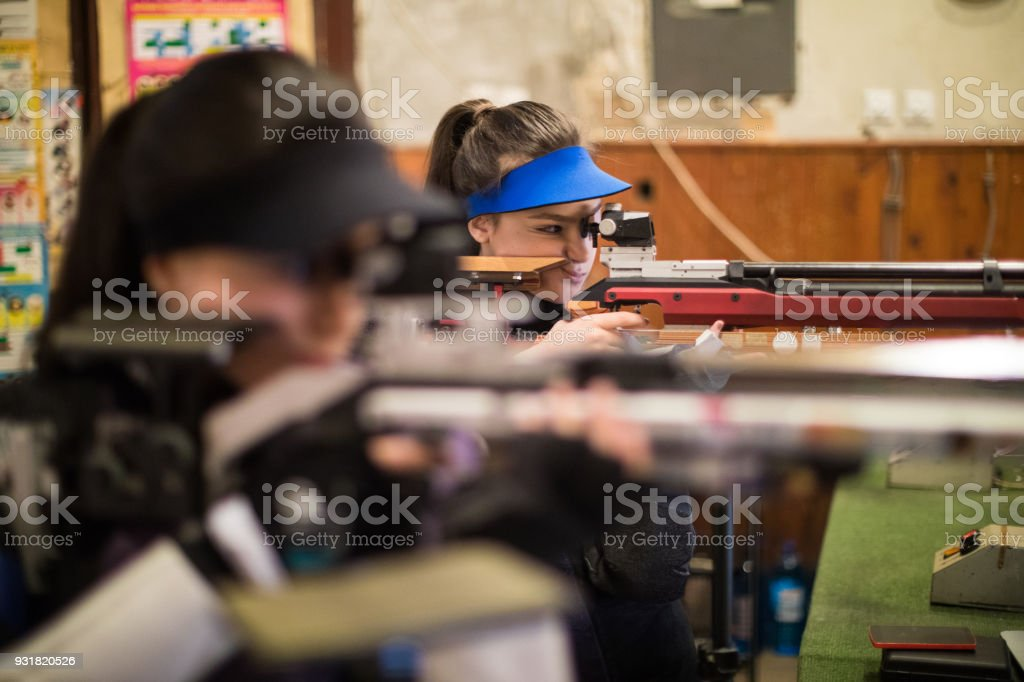 Young caucasian women practicing with sporting guns at shooting range