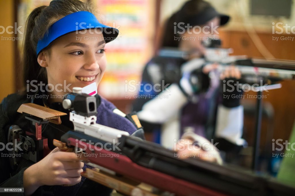 Young caucasian woman practicing with sporting gun at shooting range