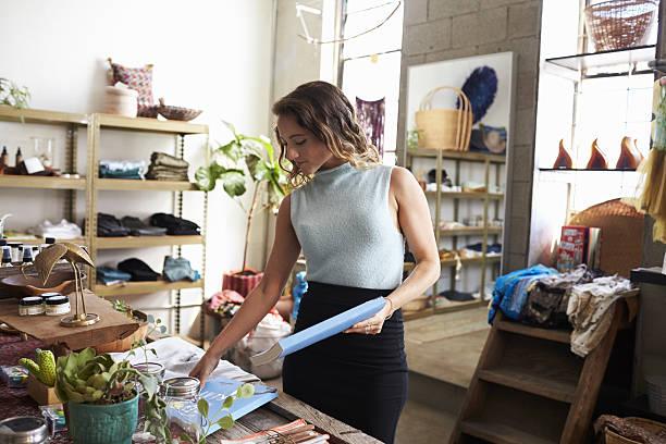 Female shop assistant arranging a clothes shop display stock photo