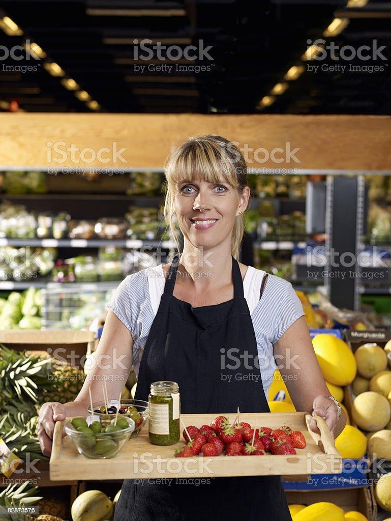 Female shop assistant showing tray of delicacies  zbiór zdjęć royalty-free