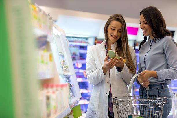 female shop assitant helps customer - drogerie stock-fotos und bilder