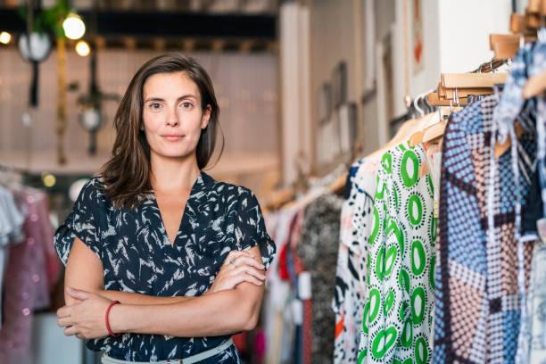 女店主用雙臂交叉在精品店裡 - small business saturday 個照片及圖片檔
