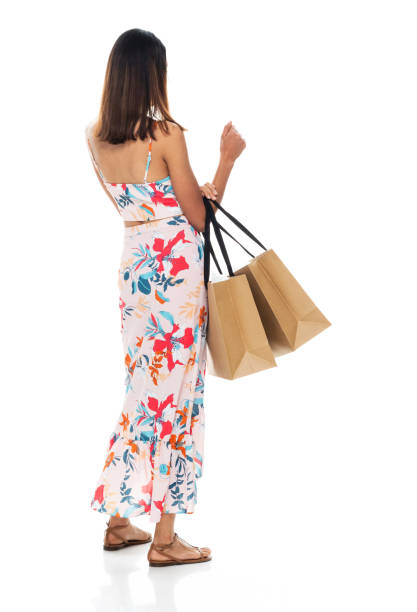 Female shopaholic standing in front of white background wearing dress and holding bag stock photo