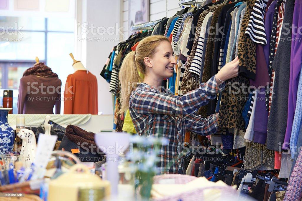 Donna shopping nel negozio di articoli di seconda mano guardando i vestiti  foto stock royalty- 3cab310eec1