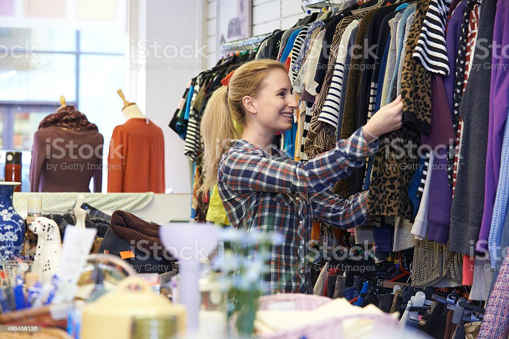 Female Shopper In Thrift Store Looking At Clothes stock photo