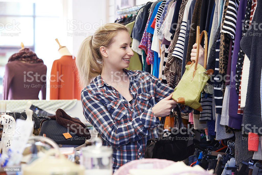 Female Shopper In Thrift Store Looking At Handbags​​​ foto