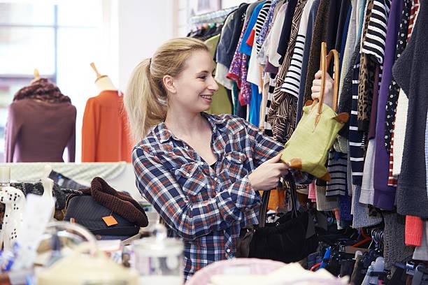 Mujer de compras en la tienda de artículos de segunda mano buscando en los bolsos - foto de stock