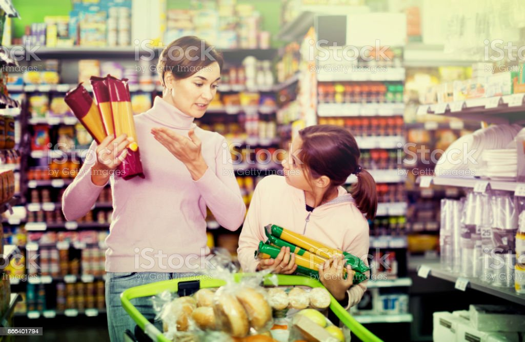 Female shopper with teenage daughter searching for pasta stock photo