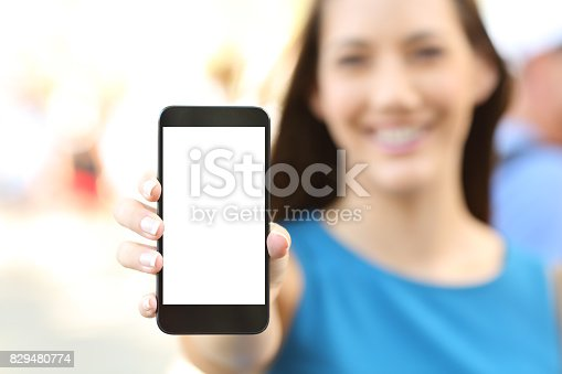 istock Female showing a blank vertical phone screen 829480774