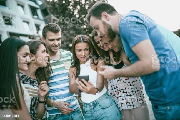 Female Showing Her Colleagues Funny Photos On Smartphone - Fotografias de stock e mais imagens de A usar um telefone