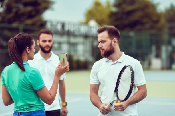 Female Showing New Tennis Court Training Timetable To Male On Smartphone stock photo
