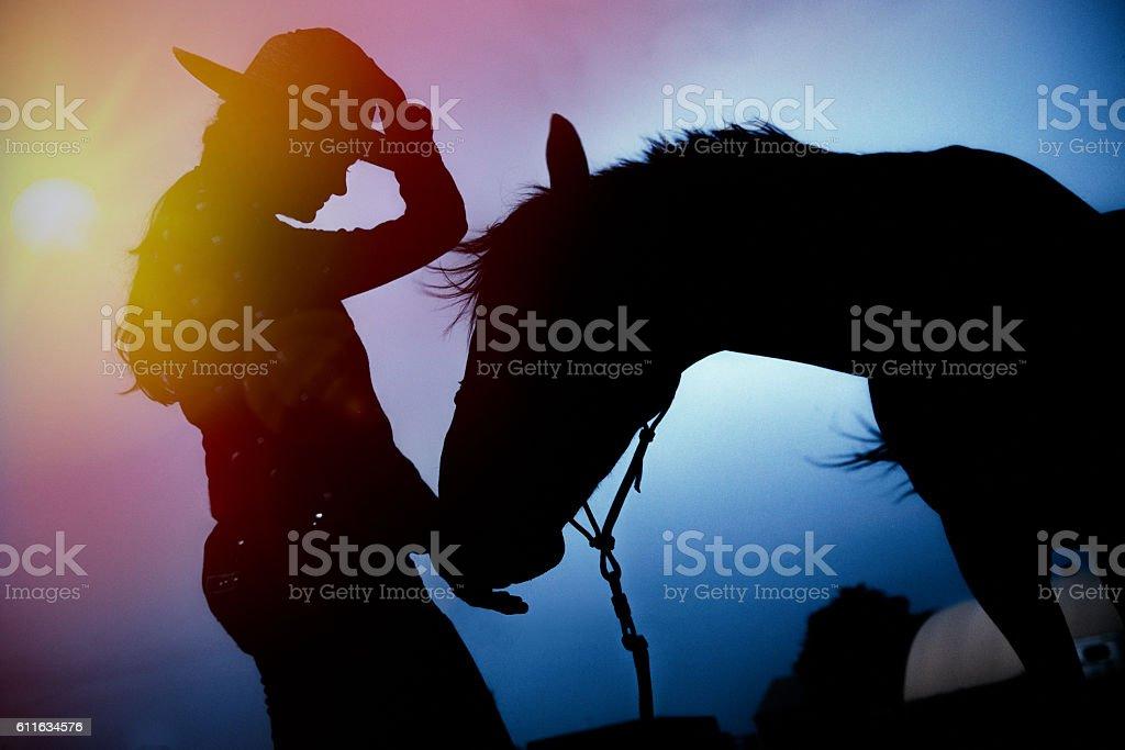 Female silhouette at sunset feeding horse stock photo