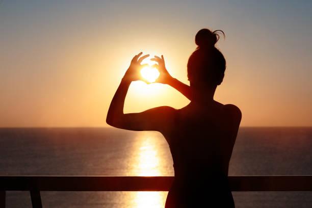 Weibliche Silhouette auf dem Balkon macht Herzenszeichen Geste – Foto