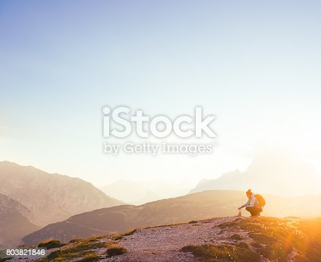 istock Female silhouette finding her inner peace in breathtaking mountain environment during sunrise 803821846