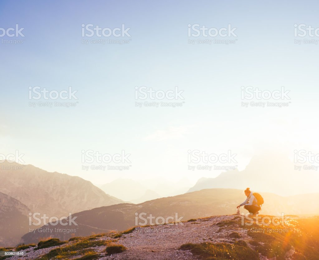 Female silhouette finding her inner peace in breathtaking mountain environment during sunrise stock photo