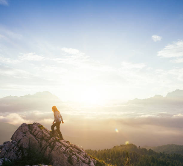 Female silhouette on top of mountain peak during sunrise Female silhouette on top of mountain peak during sunrise surrounded by surreal soft clouds floating below single step stock pictures, royalty-free photos & images