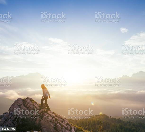 Photo of Female silhouette on top of mountain peak during sunrise